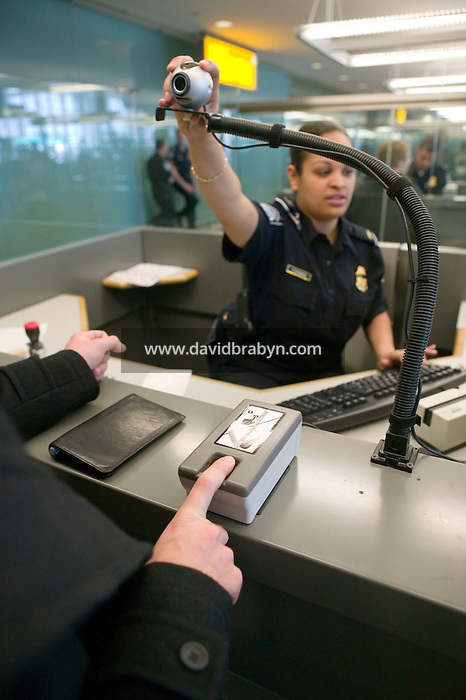 11 April 2006 - New York City, NY - CBP officer Aja Stephens (R) adjusts a camera to photograph an incoming passenger (L, hidden) as the fingerprint scanning is completed at a passport control station at JFK airport in the Queens borough of New York City, USA, 11 April 2006.