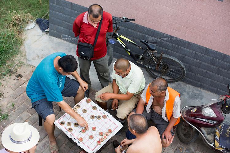 Men play Xiangqi, or Chinese Chess, on a sidewalk in Xian, Shaanxi, China.