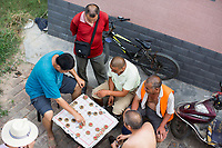 Men play Xiangqi, or Chinese Chess, on a sidewalk in Xian, Shaanxi, China.