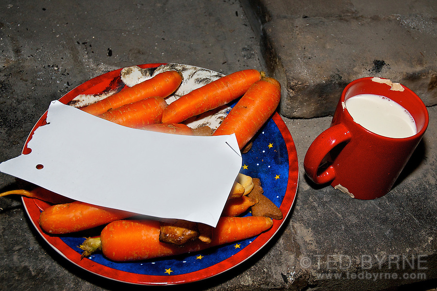 Cookies and milk for Santa, carrots for reindeer; in a rustic chimney, with a blank note