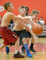 NWA Democrat-Gazette/ANDY SHUPE<br /> Roman Simpson (from left), 8, of Fayetteville; Cole Mcgarrah, 9, of Prairie Grove; and Skye Davenport, 10, of Fayetteville; reach Saturday, March 10, 2018, for a loose ball while playing games at Arkansas Athletes Outreach in Fayetteville. The longtime organization hosted a community block party meant to build bridges between area youth and the law enforcement community which participated by cooking and helping with games.