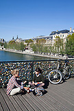 FRANCE, Paris, Ladies resting on the Pont des Arts overlooking the Royal Palace in background