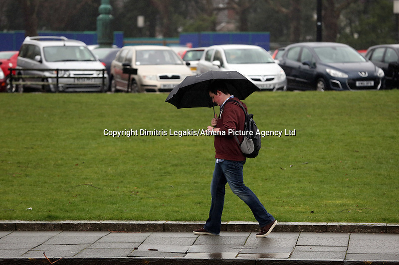 WEATHER PICTURE WALES<br /> Pictured: A man with an umbrella in Swansea, south Wales. Friday 14 February 2014<br /> Re: More strong winds have been forecast and severe flood warning issued for parts of the UK.