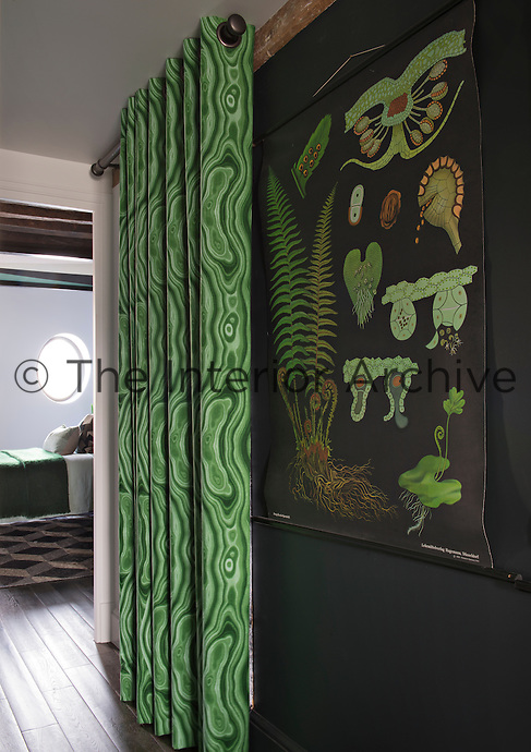 A bold colour approach of black and shades of grey is offset with items in varying shades of green, such as the geometric patterned curtains hanging in the hallway.