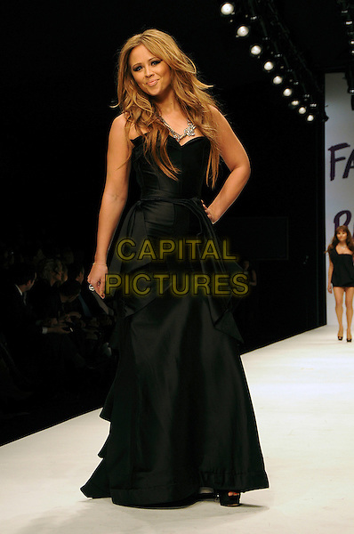 KIMBERLEY WALSH.The Fashion For Relief Haiti 2010 show for London Fashion Week Autumn/Winter 2010 at Somerset House, London, England..February 18th, 2010.LFW catwalk runway full length black maxi dress gathered hand on hip kimberly .CAP/CAS.©Bob Cass/Capital Pictures.