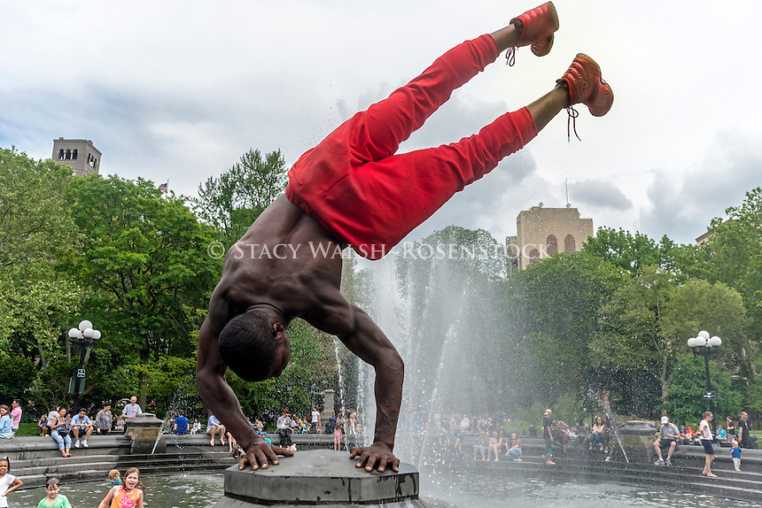 New York, NY - 30 May 2016 - Man doing a handstand near the fountain in Washington Square Park, on Memorial Day Weekend. ©Stacy Walsh Rosenstock