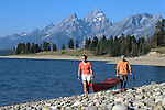 A couple carries a sea kayak on the shore of Jackson Lake in Grand Teton National Park, Jackson Hole, Wyoming.