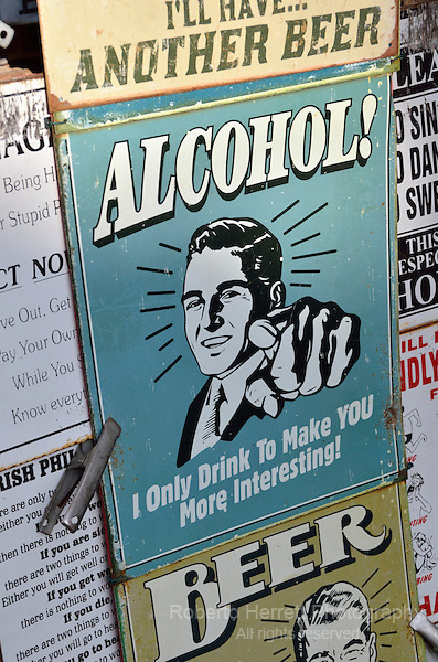 'Alcohol! I only drink to make you more interesting' tin sign in a street market stall