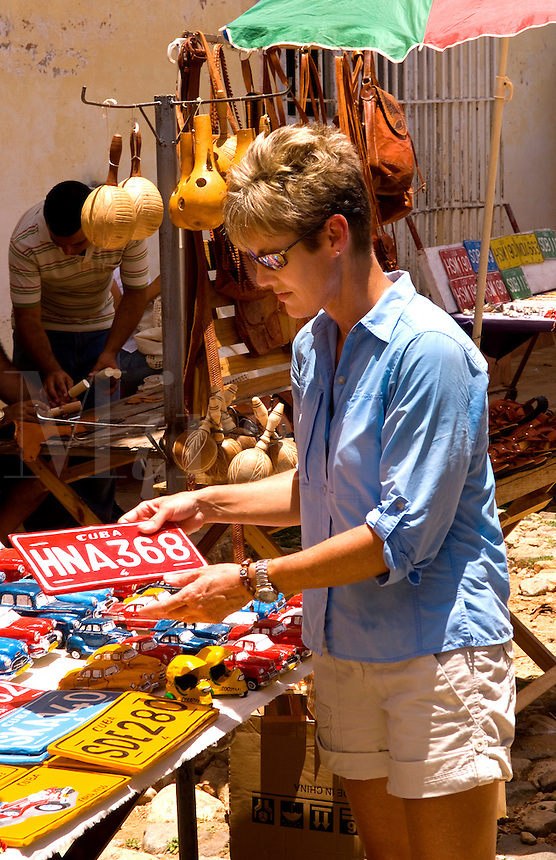 Tourist woman buying souvenirs of plates and old cars in street shop of the old colonial city of Trinidad in Cuba