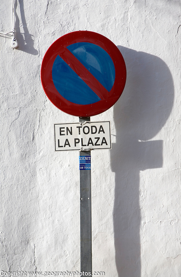 Close up of parking restriction sign against white wall in the old city of Ronda, Spain