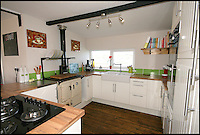 BNPS.co.uk (01202 558833)<br /> Pic: RiverSales&amp;Lettings/BNPS<br /> <br /> ****Please use full byline****<br /> <br /> Galley.<br /> <br /> A 100-year-old barge once used to ship cargo up and down the River Thames has been transformed into a plush four-bedroom house that is now on the market for &pound;450,000.<br /> <br /> The 90ft boat was salvaged from the banks of Thames in the 1970s and turned into a floating dormitory for schoolchildren at an outdoor activity centre.<br /> <br /> But it has since been given a complete makeover and now looks more like a cosy country cottage than a boat.<br /> <br /> The two-storey houseboat runs off mains electricity, has wifi access, electric heating, and hot water, and it also has a reserve water tank stored in its funnel.<br /> <br /> And buyers can count the picturesque River Hamble near Southampton, Hants, as their back garden.