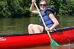 Young woman paddling a canoe on the Fox River in Yorkville Illinois