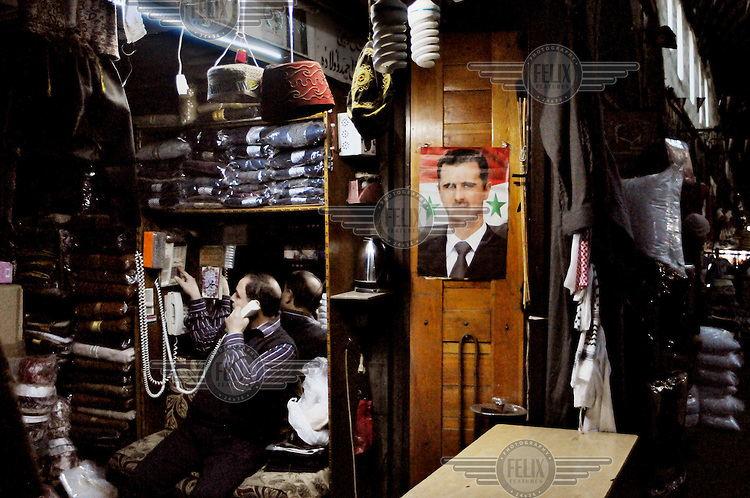 A portrait of president Bashar al-Assad on the wall of  a small clothes shop.