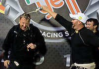 Nov 10, 2013; Pomona, CA, USA; Ted Yerzyk (left) gets doused with beer by NHRA top fuel dragster driver and world champion Shawn Langdon as he celebrates after winning the Auto Club Finals at Auto Club Raceway at Pomona. Mandatory Credit: Mark J. Rebilas-
