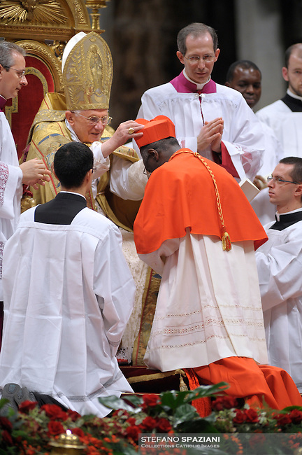 Guinean newly appointed Cardinal Robert Sarah (C) gets his biretta, the square red hat symbolising the blood of the martyrs, from Pope Benedict XVI (L) on November 20, 2010 during a consistory at St Peter's basilica at The Vatican. 24 Roman Catholic prelates join today the Vatican's College of Cardinals, the elite body that advises the pontiff and elects his successor upon his death