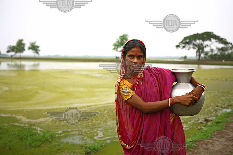 Women carrying vessels filled with water that has been collected from a special tank that stores and filters pond water...