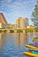 Congress Bridge in downtown Austin with water biker heading out Lady Bird Lake on this day. We loved the clouds that just seem to billow as the late afternoon sun turns the bridge a golden colof.