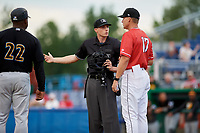 Batavia Muckdogs manager Mike Jacobs (17) talks with home plate umpire Tyler Witte as manager Kieran Mattison (22) looks on during a game against the West Virginia Black Bears on June 19, 2018 at Dwyer Stadium in Batavia, New York.  West Virginia defeated Batavia 7-6.  (Mike Janes/Four Seam Images)