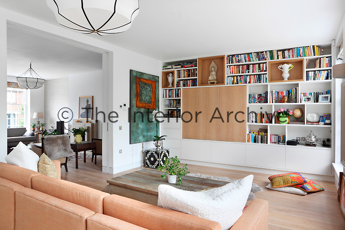 An informal sitting room with floor to ceiling bookshelves and a wooden panel that conceals a television.
