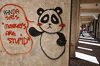 "Romania. Iași County. Iași. Graffiti on the wall: "" Panda says. Monkeys are stupid "". Amanual worker is carrying a table in his arms. Iași (also referred to as Iasi, Jassy or Iassy) is the largest city in eastern Romania and the seat of Iași County. Located in the Moldavia region, Iași has traditionally been one of the leading centres of Romanian social, cultural, academic and artistic life. The city was the capital of the Principality of Moldavia from 1564 to 1859, then of the United Principalities from 1859 to 1862, and the capital of Romania from 1916 to 1918. 8.06.15© 2015 Didier Ruef"