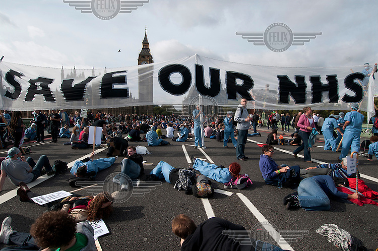 Protesters lie down on the road under a banner that reads: 'Save our NHS' during a blockade of Westminster Bridge, one of the main routes that lead to Parliament, London. It was organised by UK Uncut to protest the Health and Social Care Bill due to go before Parliament three days later.