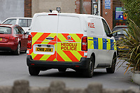 "Pictured: A police van in the car park next to the Lloyds Bank on the High Street of Gorseinon, Wales, UK. Tuesday 20 November 2018<br /> Re: Two men with machetes are being hunted by police after trying to rob a Lloyds Bank in Gorseinon, near Swansea.<br /> Armed officers, police dogs and helicopter responded to the armed robbery at 10:00am on Tuesday.<br /> According to witnesses reports, the robbers ""came through the ceiling"" and held a member of staff by the throat.<br /> South Wales Police said nobody was hurt during the incident.<br /> A witness said: ""They had a girl from Lloyds by the throat. After robbing the bank they used a car to drive off."""