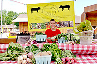 RACHEL DICKERSON/MCDONALD COUNTY PRESS Quinten Thurlo, 8, of Thurlo Family Farms, stands in for his mother, Jen Thurlo, at the Pineville Farmers Market on June 4. The family was selling green onions, potatoes, squash, parsley, lettuce, turnips, radishes, and basil. The farm is located one-eighth of a mile south of Bluff Dwellers Cave.