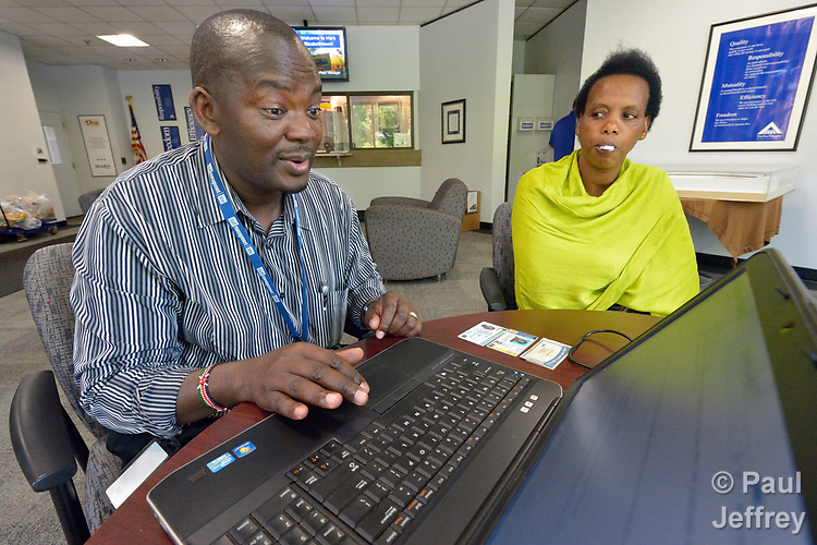 Joseph Shilalo, an employment specialist with Church World Service, helps Felecite Mukagatana fill out an online job application at the Mars factory in Elizabethtown, Pennsylvania. Mukagatana, who has an drug testing swab in her mouth, is a refugee from the Democratic Republic of the Congo who was resettled in Lancaster, Pennsylvania, by Church World Service. She passed the drug test and got a job at the factory.<br /> <br /> Photo by Paul Jeffrey for Church World Service.