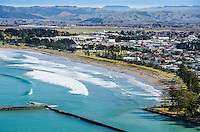 Surf breakers on  Gisborne foreshore with  city centre behind. North Island New Zealand.