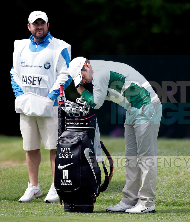 Paul Casey of England rests his head on his clubs while waiting to play his next shot