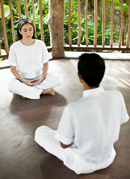 A woman meditates with an instructor in The Spa's Yoga Pavilion at Six Senses Hideaway Yao Noi. Thailand.
