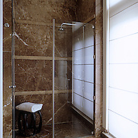 A corner of the brown marble bathroom is occupied by a spacious glass and stainless steel walk-in shower