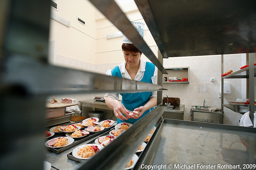 Cooks in the two large cafeterias at the Chernobyl plant prepare lunch en masse for 3,800 workers daily. Although the kitchen staff complain about low salaries, they have few other options for employment. <br /> ------------------- <br /> This photograph is part of Michael Forster Rothbart's After Chernobyl documentary photography project.<br /> © Michael Forster Rothbart 2007-2010.<br /> www.afterchernobyl.com<br /> www.mfrphoto.com <br /> 607-267-4893 o 607-432-5984<br /> 5 Draper St, Oneonta, NY 13820<br /> 86 Three Mile Pond Rd, Vassalboro, ME 04989<br /> info@mfrphoto.com<br /> Photo by: Michael Forster Rothbart<br /> Date:  2/2009    File#:  Canon 5D digital camera frame 57829<br /> ------------------- <br /> Original caption: <br /> The Chernobyl Nuclear Power Plant (ChNPP or ChAES) is the site of the world's worst nuclear accident. On the night of April 26, 1986, the Fourth Block reactor exploded during a safety test, sending radioactive particles into the atmosphere and eventually around the world. The population within 30 kilometers was permanently evacuated, including residents of Pripyat and many villages. Although ChAES stopped generating electricity in December 2000, today 3,800 employees continue to work at the plant, commuting from the new city of Slavutych (population 24,300), which was built after the accident to replace Pripyat.