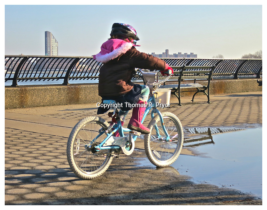YORKVILLE, NY - FEBRUARY 15: Photograph of girl cycling through puddle on Finley Walk in Carl Schurz Park on the East River taken in Yorkville, New York on February 15, 2013. Photo Credit: Thomas R. Pryor
