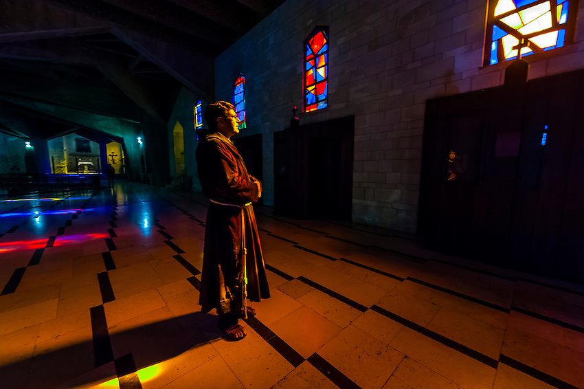 A Franciscan friar surrounded by reflections from stained glass in the Basilica of the Annunciation, Nazareth, Israel.