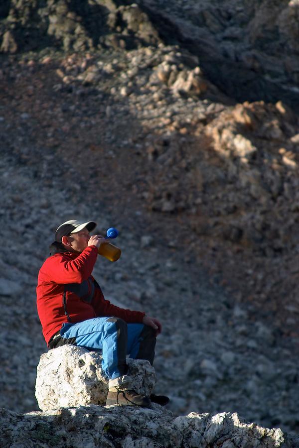 Man sitting on boulder drinking from water bottle, Grand Teton Lower Saddle, Grand Teton National Park, Teton County, Wyoming, USA