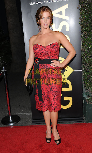 POPPY MONTGOMERY  .at G'Day USA LA Black Tie Gala held at The Hollywood Palladium in Hollywood, California, USA, January 22nd, 2011..full length red strapless dress hand on hip black brooch clutch bag open toe shoes peep lace .CAP/RKE/DVS.©DVS/RockinExposures/Capital Pictures.