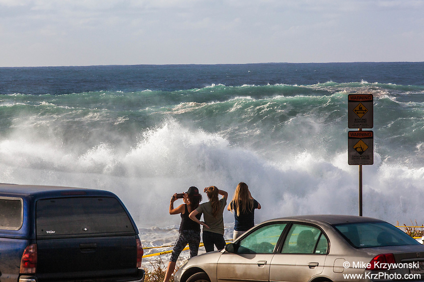 Spectators watching giant waves during a large winter swell at Shark's Cove, North Shore, Oahu