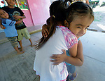 In Zapotal, Mexico, 3-year old Luz Elena Martinez goes to preschool one hour a day to help prepare her to go full time the following year. In this image, the girl, who is blind, is hugging her older sister, 5-year old Sandra, during a dance by the students. Sandra will graduate from preschool the coming year, but before that she's getting Luz accustomed to the school environment to make for an easier transition next year.