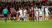 Match referee Andrew Marriner (L) attempts to diffuse an argument that broke out between Swansea and Bournemouth players during the Barclays Premier League match between Swansea City and Bournemouth at the Liberty Stadium, Swansea on November 21 2015