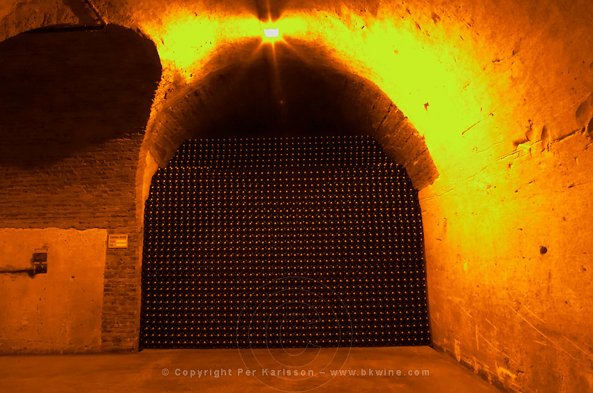 In the underground winecellar that is an old chalk quarry: thousands and millions of bottles aging, stacked high in a vault, Champagne Ruinart, Reims, Champagne, Marne, Ardennes, France, low light grainy grain