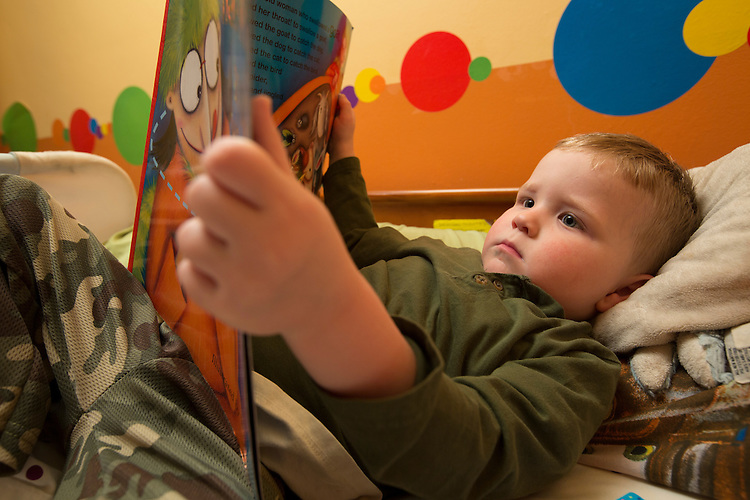 Nathan looks through the book There Was an Old Woman Who Swallowed a Fly before going to bed. Every night Sarah lets the triplets choose three books each to flip through.