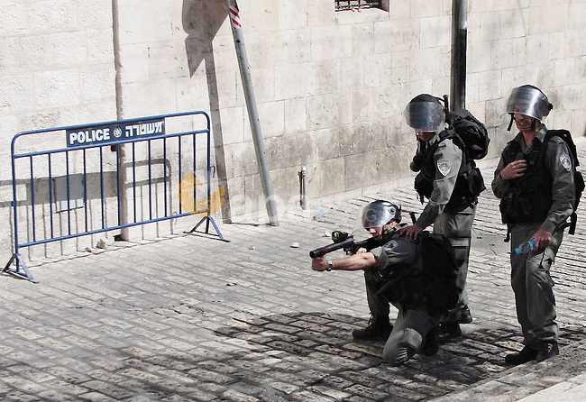 An Israeli border police officer prepares to fire a tear gas canister at Palestinian stone-throwers, during clashes between Israeli police and Palestinians in Jerusalem's Old City, Sunday, Sep. 27, 2009. Israeli police used stun grenades Sunday to disperse Palestinian rioters at a volatile Jerusalem site holy to Jews and Muslims, police said. The incident took place during a visit by a Jewish group to the compound in Jerusalem's Old City known to Jews as the Temple Mount and to Muslims as the Noble Sanctuary. Photo by Mohamar Awad