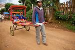 pousse pousse in Antsirabe streets...pousse pousse dans les rues de Antsirabe. Ce moyen de locomotion daterait de l arrivee des Chinois  a Madagascar, venus pour la construction de la ligne de chemin de fer au debut du vingtieme siecle