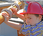 A young visitor tries his hands at the tiller of the Sloop Clearwater at the Pumpkin Sail Festival at Hudson, NY on Monday, October 10, 2011. Photo by Jim Peppler. Copyright Jim Peppler/2011.