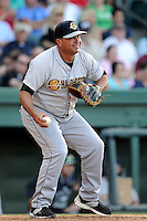 Manager Luis Dorante (25) of the Charleston RiverDogs takes warmup pitches in a game against the Greenville Drive on Sunday, May 24, 2015, at Fluor Field at the West End in Greenville, South Carolina. Charleston won 3-2. (Tom Priddy/Four Seam Images)