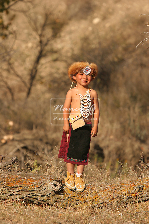 A young Native American Indian boy standing on a log