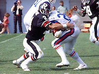 Larry Brune of the Ottawa Rough Riders tackles Montreal Alouettes David Green. Photo Scott Grant