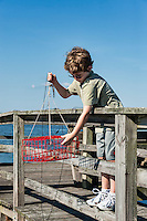 Young boy crabbing from the dock, Outer Banks, North Carolina, USA