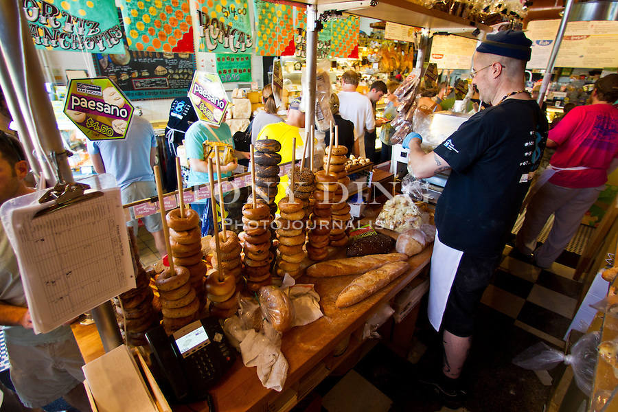 Spools of bagels share tight counter space at the bakery station inside a jam-packed Zingerman's Deli, Friday, Sept. 2, 2011 in Ann Arbor, Mich. (Tony Ding for The New York Times)